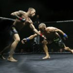 Windham native Jamie Harrison (right) reaches for a takedown attempt against Bruce Boyington during their NEF XVII mixed martial arts main event at the Androscoggin Bank Colisee in Lewiston, April 11, 2015.
