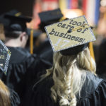"An unidentified Husson University graduation uses her mortarboard to show that she ""took care of business"" during the 2017  commencement at the Cross Insurance Center."