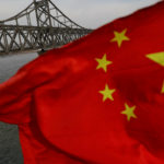 A Chinese flag is seen in front of the Friendship bridge over the Yalu River connecting the North Korean town of Sinuiju and Dandong in China's Liaoning Province on April 1, 2017.