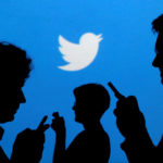 People holding mobile phones are silhouetted against a backdrop projected with the Twitter logo in this illustration picture taken, Sept. 27, 2013.