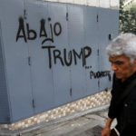 "A man walks past a graffiti in Caracas, Venezuela, Aug. 13, 2017. The graffiti reads: ""Down with Trump ... Rot."""
