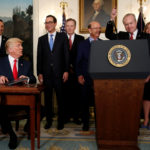 U.S. President Donald Trump gives a pen to Raytheon CEO Tom Kennedy (2nd R) after signing a memorandum directing the U.S. Trade Representative to complete a review of trade issues with China at the White House in Washington, U.S. August 14, 2017.