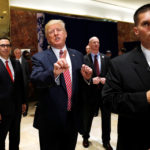 "President Donald Trump stops to respond to more questions about his responses to the violence, injuries and deaths at the ""Unite the Right"" rally in Charlottesville as he walks away flanked by U.S. Treasury Secretary Steven Mnuchin (L) and U.S. Secret Service agents (R) after speaking to the media in the lobby of Trump Tower in Manhattan, New York, U.S., August 15, 2017."