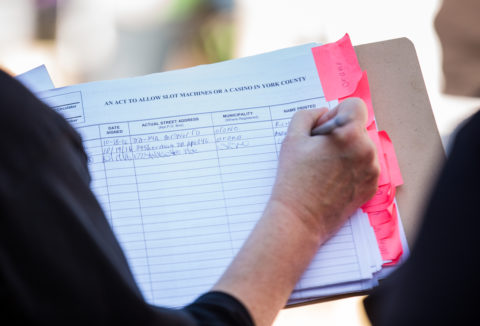 A person signs a petition that is related to &quotAn Act to Allow Slot Machines or a Casino in York County&quot in October 2016 in Bangor.