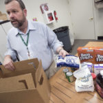 Rob Crone, director of nutrition services at Eastern Area Agency on Aging in Bangor, talks about the contents of a box of food available to low-income seniors through the Commodities Supplemental Food Program in Bangor, Feb. 14, 2017.