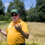 Rich Horsley talks about the barley growing in the fields during a barley workshop at the University of Maine Rogers Farm in Old Town on July 25. Farmers, researchers, brewers and maltsters attended to learn about various types of barley well suited for growing in Maine.