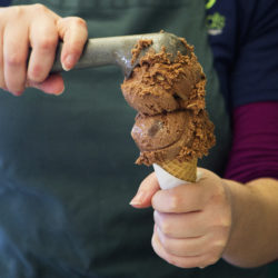 An employee scoops ice cream into a cone at Gifford's Ice Cream stand in Bangor. Gifford's has had to cope with the rising cost of vanilla beans and vanilla extract.