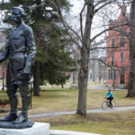 A woman cycles by the statue of Joshua Chamberlain in front of the Bowdoin College campus in Brunswick. The college announced Saturday that it will relocate a plaque listing the names of 19 alumni who fought for the Confederate Army during the Civil War.
