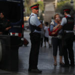 Pilar Revilla, 75, gets emotional after hugging a Catalan Mossos d'Esquadra officer after visiting an impromptu memorial where a van crashed into pedestrians at Las Ramblas in Barcelona, Spain, Aug. 20, 2017.