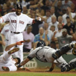 Boston's Rafael Devers slides safely past the tag of New York Yankees catcher Gary Sanchez (24) during the fifth inning of Saturday's game at Fenway Park in Boston.