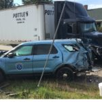A Maine state trooper suffered minor injuries after he collided with a pickup truck and tractor-trailer while responding to a burglary in progress.