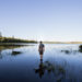 A student on the Moosehead Lake Nova trip steps out into the shallows of an area pond to look into the distant landscape for moose on August 1.