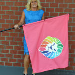 "Peggy Billings will be one of the many ""Champions"" to carry a colored flag representing the various colors of cancer during a Champion Lap preceding the Colors of Courage 5K taking place at TAMC on September 30.  She is carrying the pink flag in honor of her daughter Jessie, who is battling breast cancer."