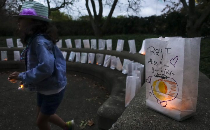 A young volunteer helps set up lights in paper bags decorated with messages for the deceased during an Out of the Darkness Walk event organized by the Cincinnati Chapter of the American Foundation for Suicide Prevention in Sawyer Point park in Cincinnati, Oct. 15, 2017.